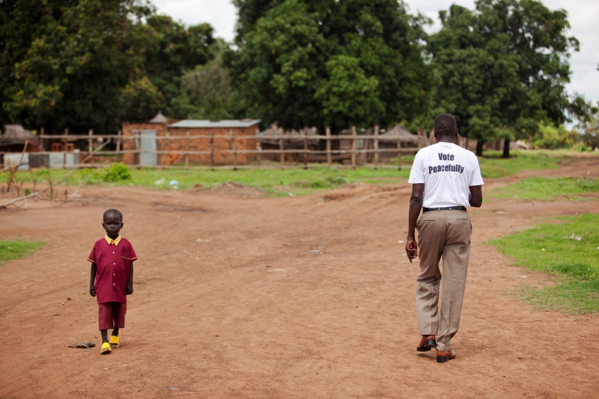 A man wearing a t-shirt to promote voting in the referendum passes a child on the way to school in Mundri, South Sudan, a week before the country gained independence.